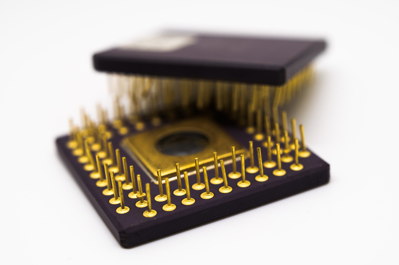 Two microprocessors with gold plated pins on a white background